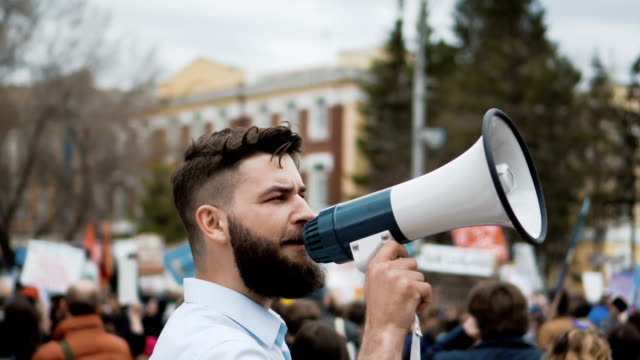 Human on the background of the crowd on the revolution. office worker 4k. Young adult angry man goes and shouts in a megaphone on strike. Caucasian guy with a beard yelling into the loudspeaker at the rally. Office worker displeased with dismissal or reduction. megaphone stock videos & royalty-free footage
