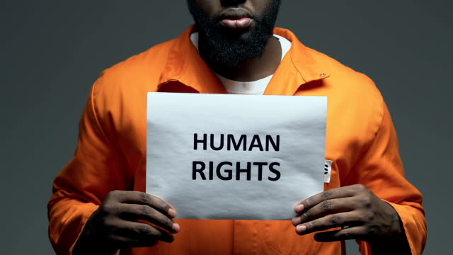 Human rights phrase on cardboard in hands of African-American prisoner, assault Human rights phrase on cardboard in hands of African-American prisoner, assault civil rights stock videos & royalty-free footage
