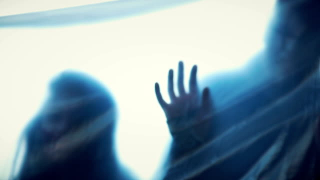 Human silhouettes behind transparent film stretching hands, scary nightmare