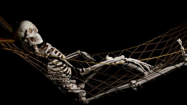 Human skeleton swingig on hammock video