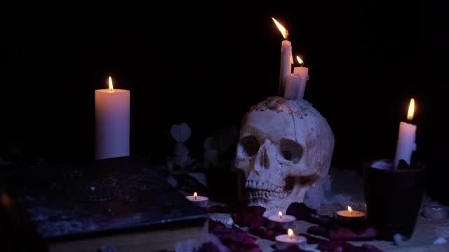 Menschlicher Schädel, Kerzen und altes Buch – Video