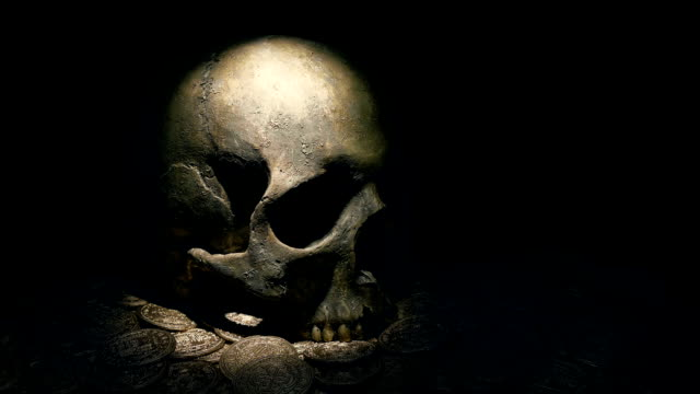 Human Skull On Gold Coins Lit Up With Torch Torch is shone on a pile of old gold coins skull stock videos & royalty-free footage
