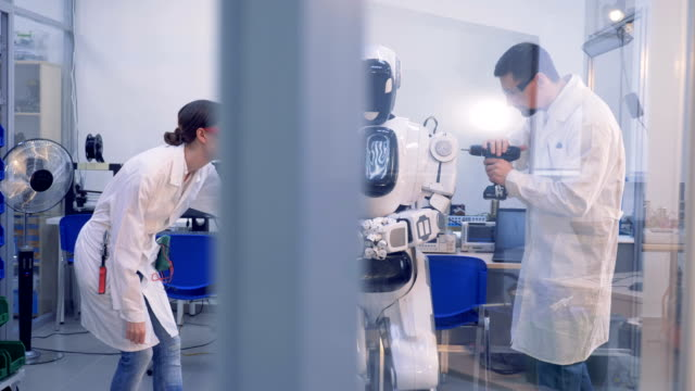 Human-like cyborg is getting checked and fixed by two engineers video