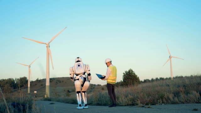 A human-like robot and a male operator are walking along the set of windmills