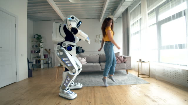 Human-like robot and a woman are dancing and jumping Human-like robot and a woman are dancing and jumping. 4K cyborg stock videos & royalty-free footage