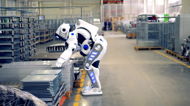 a human-like robot is putting a piece of fitting and walking away in a factory warehouse. - rivoluzione industriale video stock e b–roll