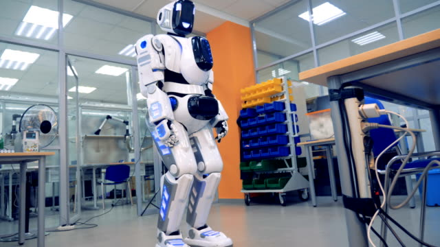 Human-like robot is rotating its head and looking into the camera video
