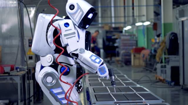 vidéos et rushes de robot humanoïde travaille avec une perceuse dans une unité de l'usine - vaisselle picto