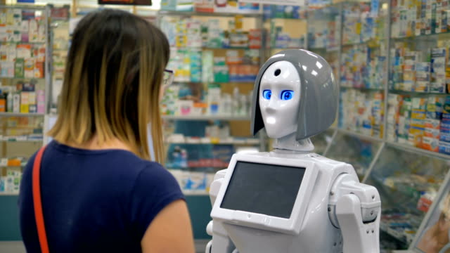 A humanoid robot consults a woman inside a drugstore. A robot stands in the center of a drugstore to assist customers. cyborg stock videos & royalty-free footage