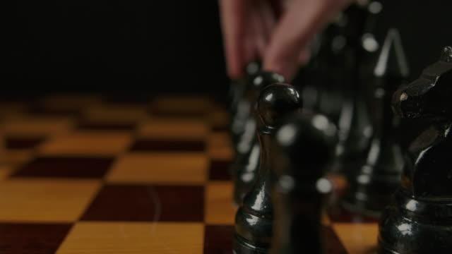 die hand des menschen macht den ersten gegner durch schwarzen bauern e7 e5 im schachspiel bewegen - könig schachfigur stock-videos und b-roll-filmmaterial