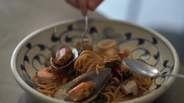 Human's hand rolling spaghetti , fried with herb and seafood , spicy