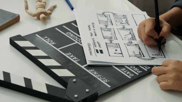 vidéos et rushes de humain est main tout en ébauchant des story-board pour faire scène de film - ardoise