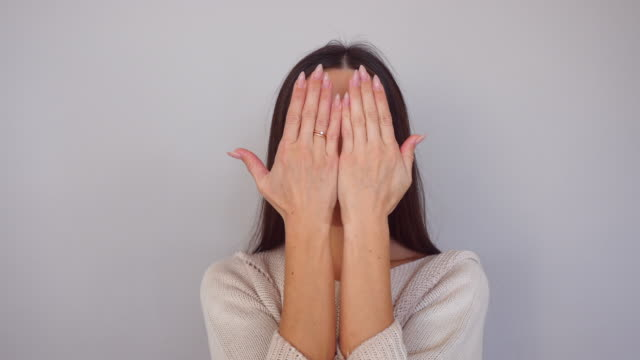 Humorous female changes facial emotions with hands video