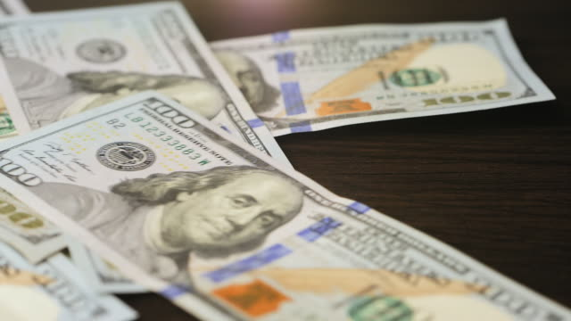 Hundred dollar bills falling on a brown wooden table Hundred dollar bills falling on a brown wooden table. Slow motion video us paper currency stock videos & royalty-free footage