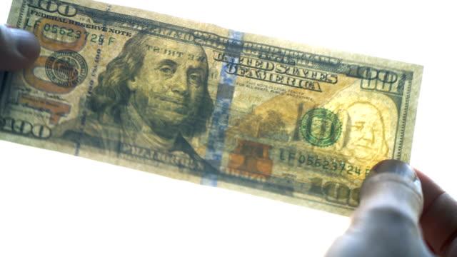 百元我們鈔票正在仔細檢查 - 人造的 個影片檔及 b 捲影像