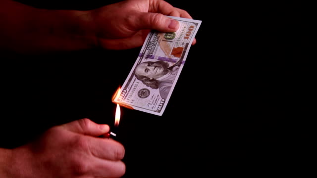 Hundred dollars bill burning in hand video