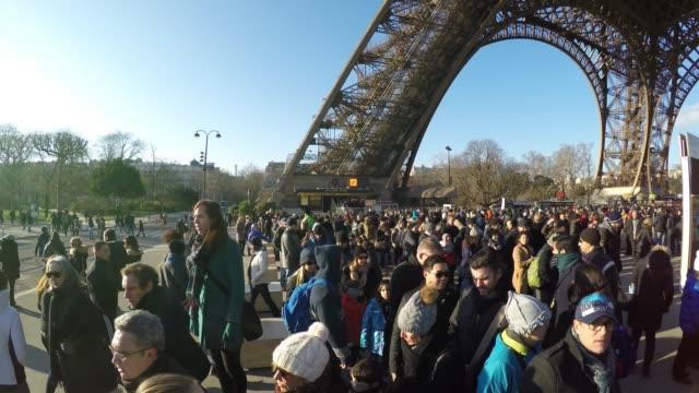 vidéos et rushes de des centaines de personnes visitant la tour eiffel à l'heure d'hiver à paris, france - tour eiffel