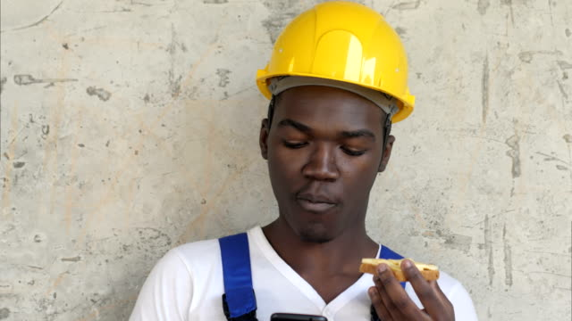 hungry afro-american worker at construction site eating sandwich lunch food looking at smartphone - craftsman architecture stock videos & royalty-free footage