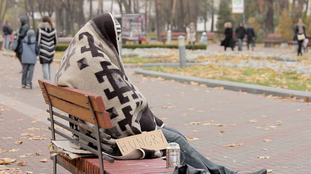 Hungry beggar sitting alone in cold park, many people passing by indifferently video