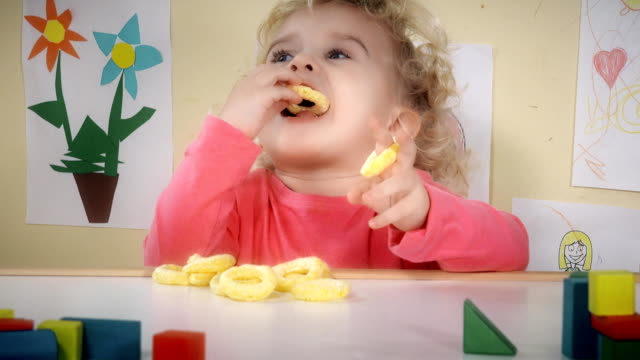 Hungry child eating corn maize crisps sitting near table in his room video