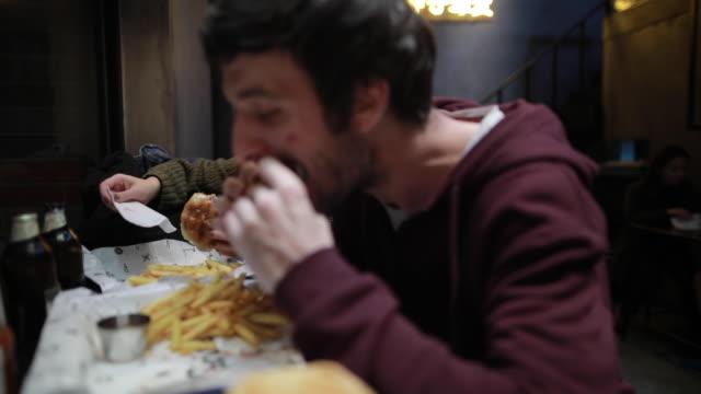 hungrige paar im fastfood-restaurant - schnellkost stock-videos und b-roll-filmmaterial