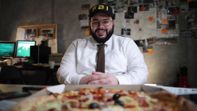 Hungry FBI detective looking at pizza in the office