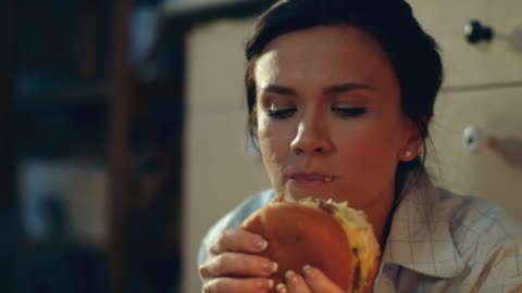 Hungry girl eating burger on floor. Young woman drinking red wine at home. Closeup hungry girl eating big burger on kitchen floor. Portrait of young woman drinking red wine evening at home floor. Joyful woman enjoying fast food dinner and wine at home in slow motion. enjoyment stock videos & royalty-free footage