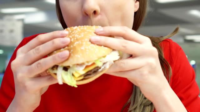 Hungry girl eating hamburger on food court. Woman biting cheeseburger at fast food restaurant video