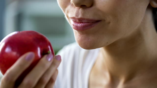 hungry girl with great appetite biting big juicy apple, healthy snack at work - mordere video stock e b–roll