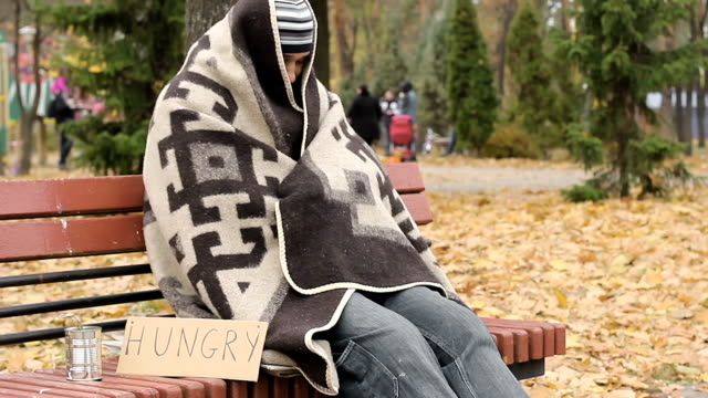 Hungry homeless frozen man sitting on bench and trying to get warm, poverty video