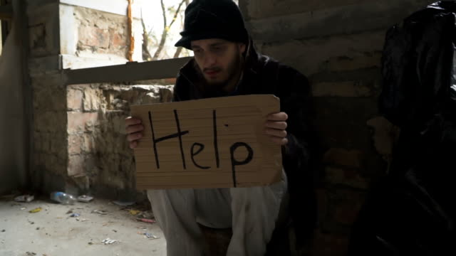 Hungry ill homeless with cardboard 'help' video