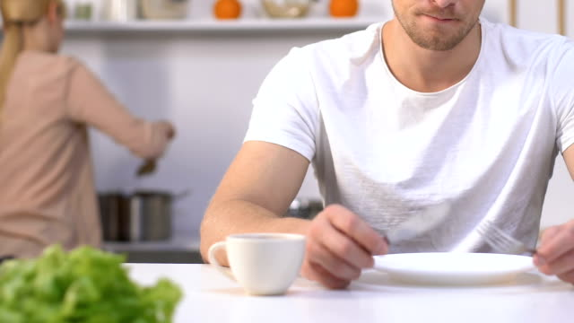 Hungry impatient husband holding knife and fork waiting for meal from slow wife Hungry impatient husband holding knife and fork waiting for meal from slow wife impatient stock videos & royalty-free footage
