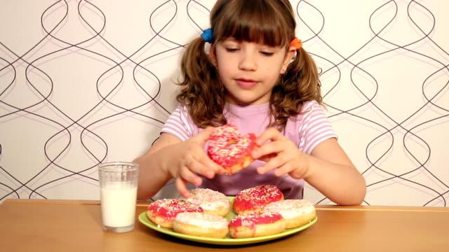 affamato bambina mangiare ciambelle - glassa video stock e b–roll