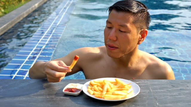 CU Hungry Man eat French Fries After Swimming 5 Shots of Hungry Asian Man eating French Fries After Swimming Exercise french fries stock videos & royalty-free footage