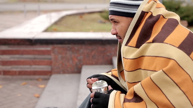 Hungry man eating canned food, homeless person sitting on ground, feeling cold video