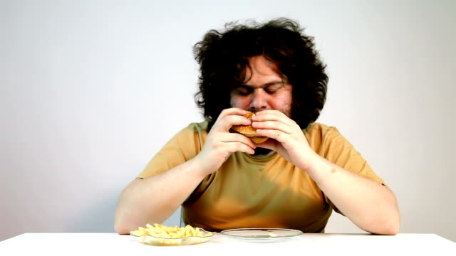 Hungry Man Eating Fast Food A hungry man eating hamburger and french fries. mouth open stock videos & royalty-free footage