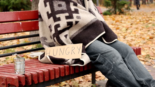 Hungry man wrapped in blanket begging, socially vulnerable homeless person video