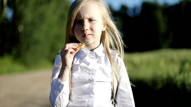 Muchacha de la escuela hambriento en camisa blanca y falda negra es caminar por el camino de arena por el campo y come una galleta. - vídeo