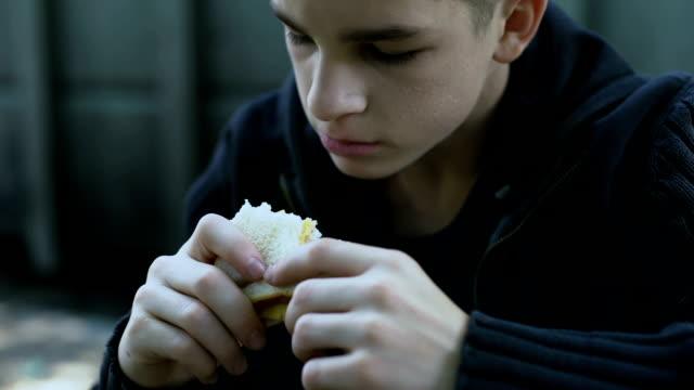 голодный подросток мальчик ест дешевый нездоровый бутерброд, низкое качество еды для ребенка - голодный стоковые видео и кадры b-roll