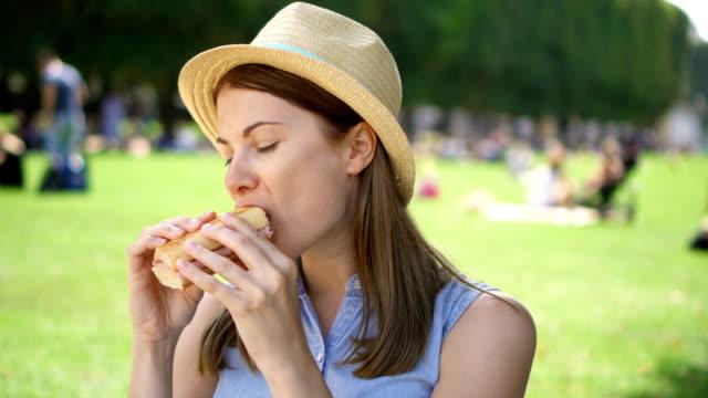 vídeos de stock e filmes b-roll de hungry woman eating baguette in park. tourist having lunch in public park enjoying summer sunny day - sanduíche