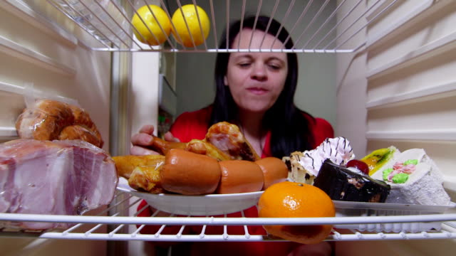 Hungry woman eating fat food inside fridge at night video