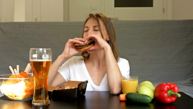 Hungry woman is happy to drink beer, eat a hamburger and french fries. She is not attracted to vegetables and fruits