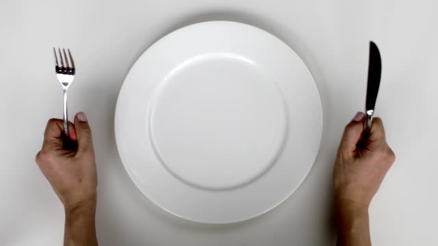 Hungry woman waiting to be served A woman is holding fork and knife. She is sitting in front of an empty plate. She is hungry and waiting to be served table top view stock videos & royalty-free footage