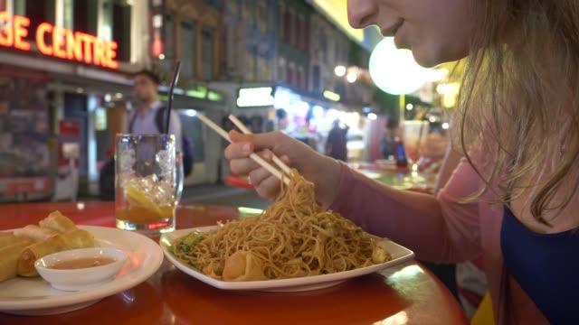vídeos y material grabado en eventos de stock de close up: hambrienta joven luchando por comer fideos con palillos de madera - gastronomía fina