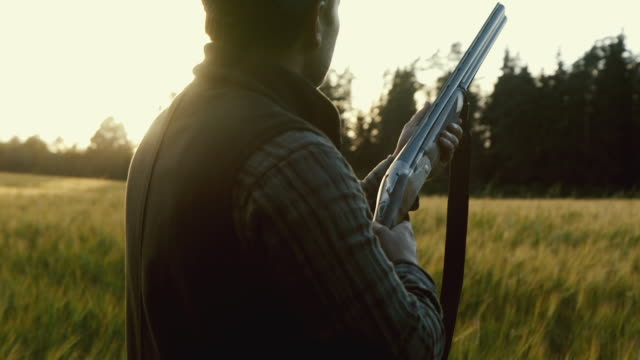 Hunter gets ready to shoot a weapon at golden hour (slow motion)