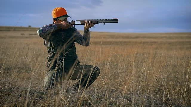 Hunter in camouflage suit sees a prey. Man aiming with his rifle for hunt. video