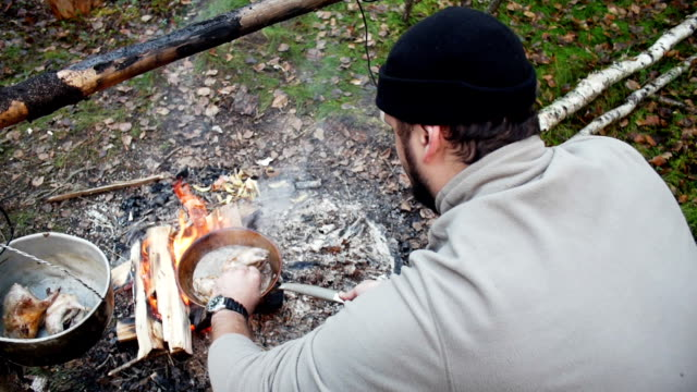 Hunter man cooks food from the fire video