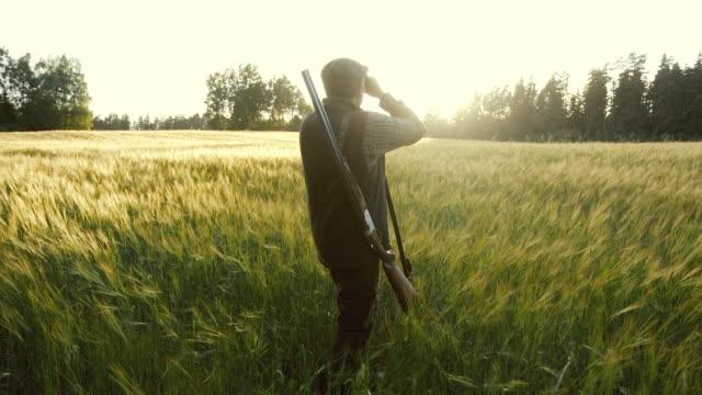 Hunter rises binoculars at golden hour
