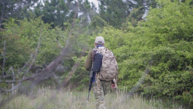 vidéos et rushes de un chasseur avec un fusil et un sac à dos va dans la forêt - chasser