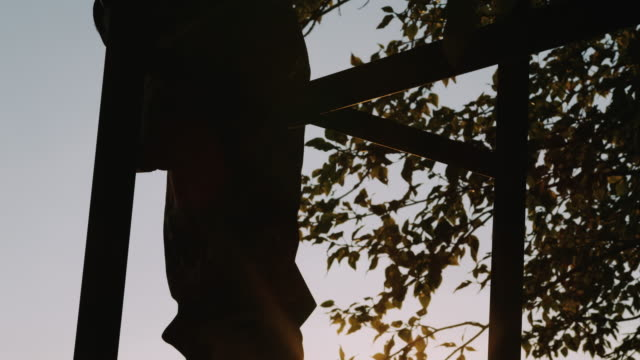 A hunters feet are followed up the ladder of the tree stand as he gets ready to hunt into the evening with the sun setting beautifully behind him in slow motion. video